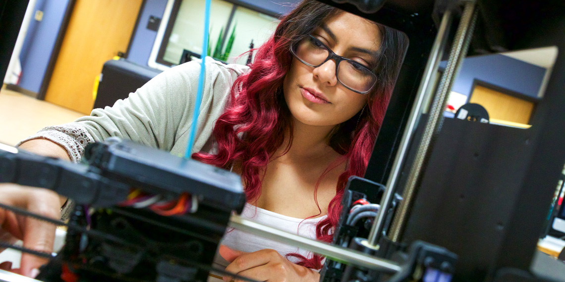 A student, in the background, uses a 3D printer, in the foreground