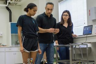 One student wearing a monitoring device on their knee stands next to a kinesiology professor while another student at a computer looks on