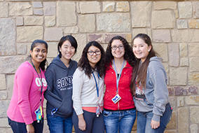 A group of female students standing in front of a rock wall