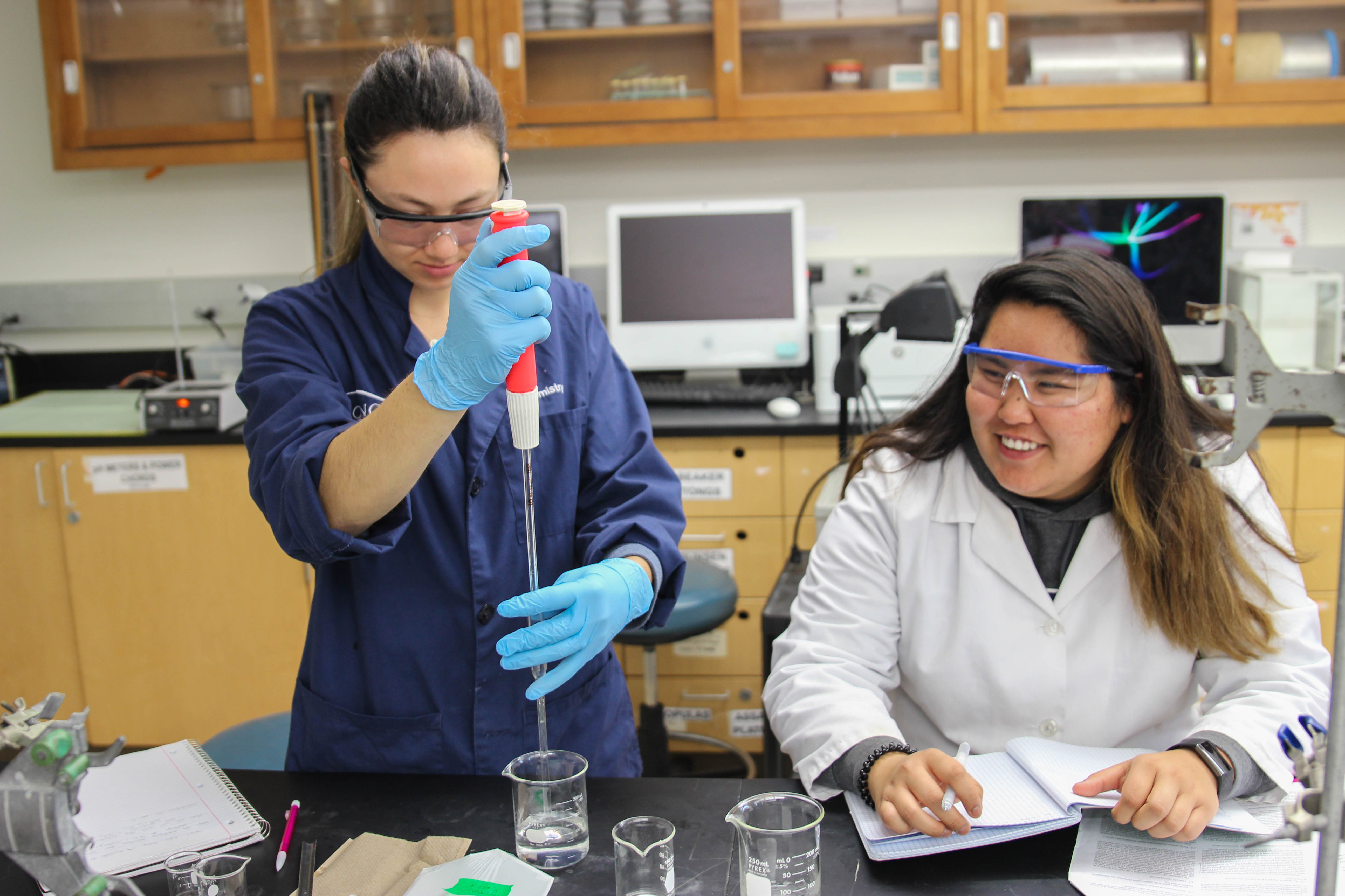 A chemistry student in a blue lab coat uses a pipette while another chemistry student takes notes