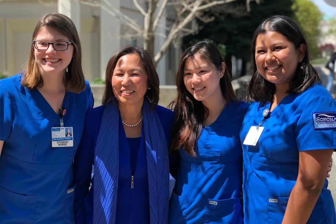 Nursing students in blue scrubs with President Judy K. Sakaki