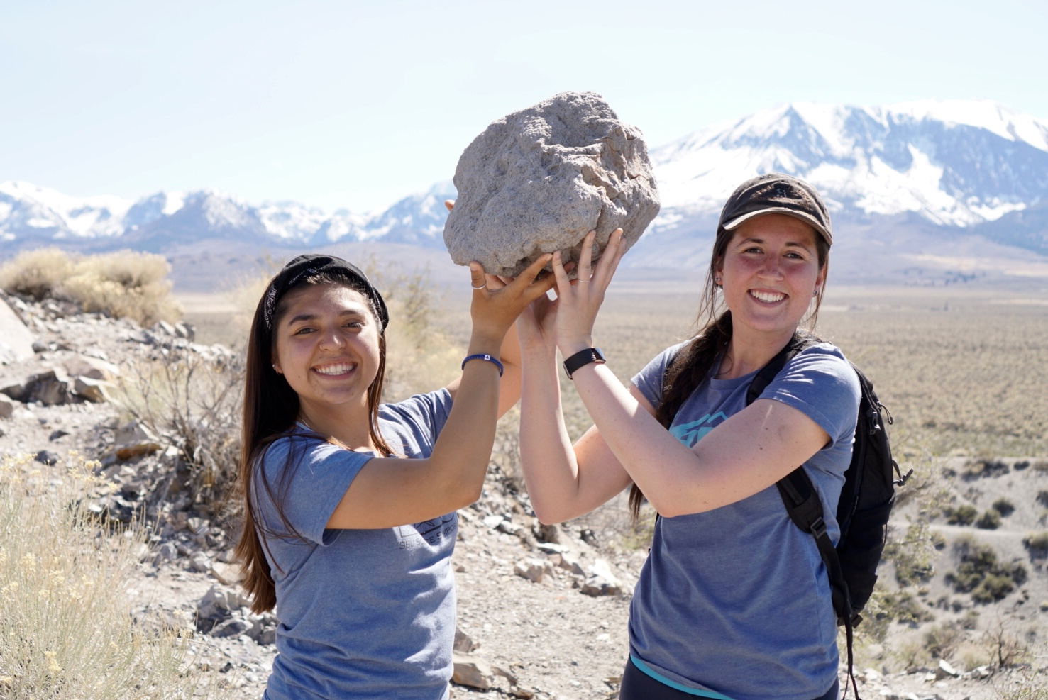 Two students hold a large rock above their heads in a dessert with snow capped mountains in the background