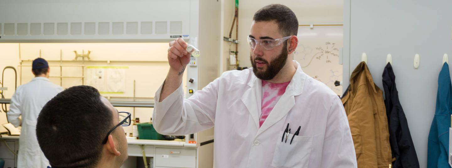 A student in lab coat and protective eyeware examines contents of a vial