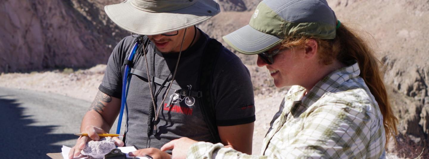 Geology professor and student looking at a rock with mountains in the background