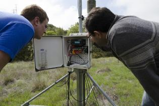 An engineering science professor looks at a piece of equipment in a green field with a student