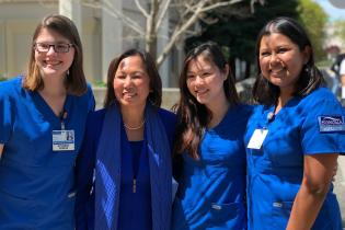 Nursing students in blue scrubs with President Judy K. Sakaki