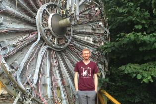 Physics student stands in front of large piece of particle physics hardware at CERN